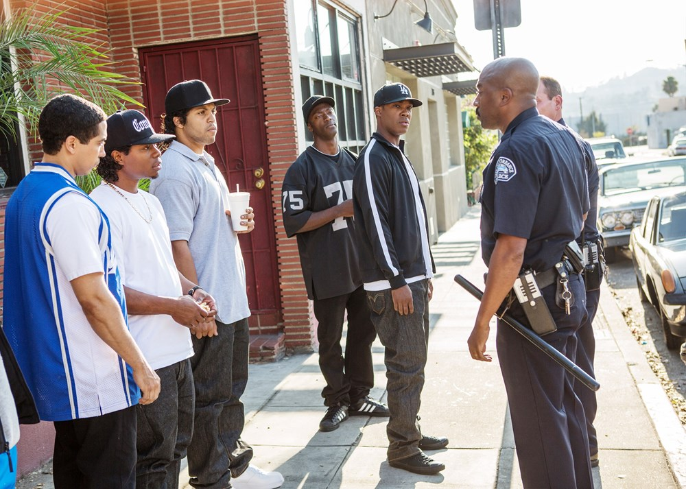STRAIGHT OUTTA COMPTON, from left, excluding police: Neil Brown Jr., as Dj Yella, Jason Mitchell, as Eazy-E, O'Shea Jackson Jr., as Ice Cube, Aldis Hodge, as MC Ren, Corey Hawkins, as Dr. Dre, 2015. ph: Jamie Trueblood/©Universal Pictures