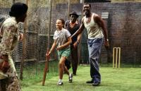 WONDROUS OBLIVION, from left: Leonie Elliott (girl holding cricket bat), Delroy Lindo (far right), 2003. ©Palm Pictures