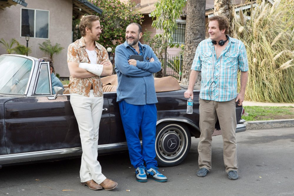 THE NICE GUYS, from left: Russell Crowe (in car), Ryan Gosling, producer Joel Silver, director Shane Black, on set, 2016. ph: Daniel McFadden/© Warner Bros.