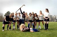 ST. TRINIAN'S, foreground, reading: Juno Temple; standing: Paloma Faith (hockey stick aloft), Gemma Arterton (dark pageboy), Kathryn Drysdale (third from right), Talulah Riley (far right), 2007, ©NeoClassics Films