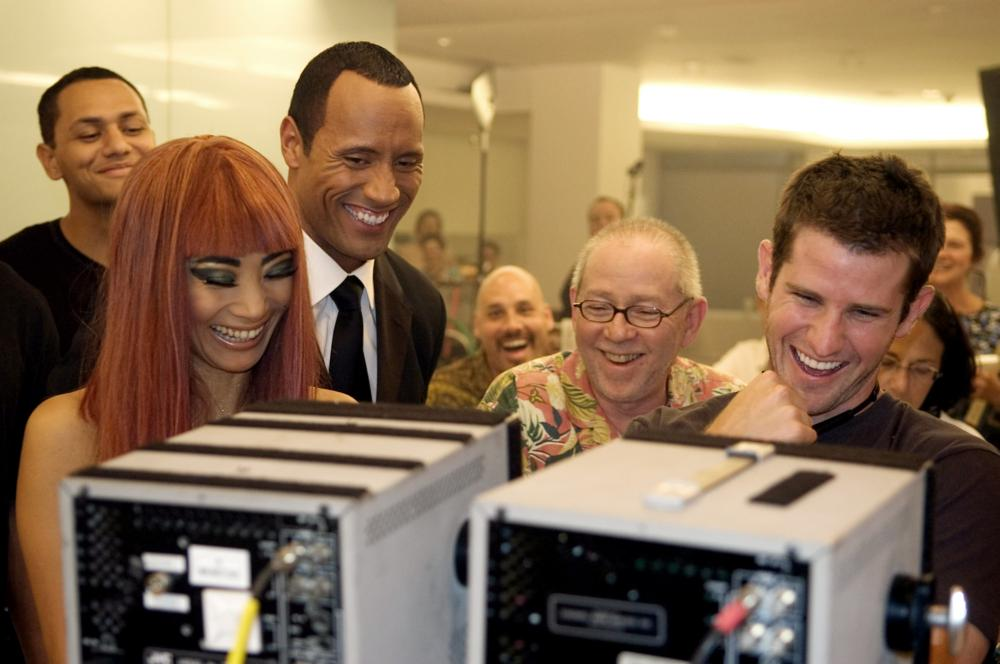 SOUTHLAND TALES, foreground: Bai Ling (far left), The Rock (second from left), director Richard Kelly (far right), on set, 2006. ©Universal