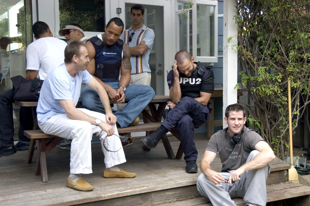 SOUTHLAND TALES, foreground: The Rock (second from left), Seann William Scott (third from left), director Richard Kelly (far right), on set, 2006. ©Universal