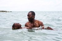 MOONLIGHT, Mahershala Ali, holding Alex R. Hibbert, 2016, photo by David Bornfriend, ©A24