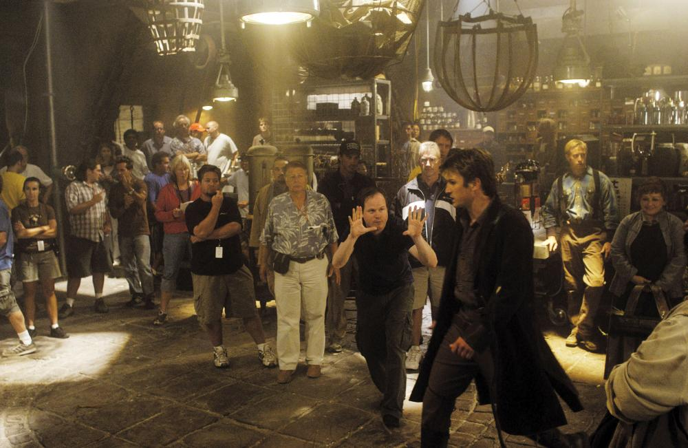 SERENITY, director Joss Whedon (front left), Nathan Fillion (front right), on set, 2005. ©Universal