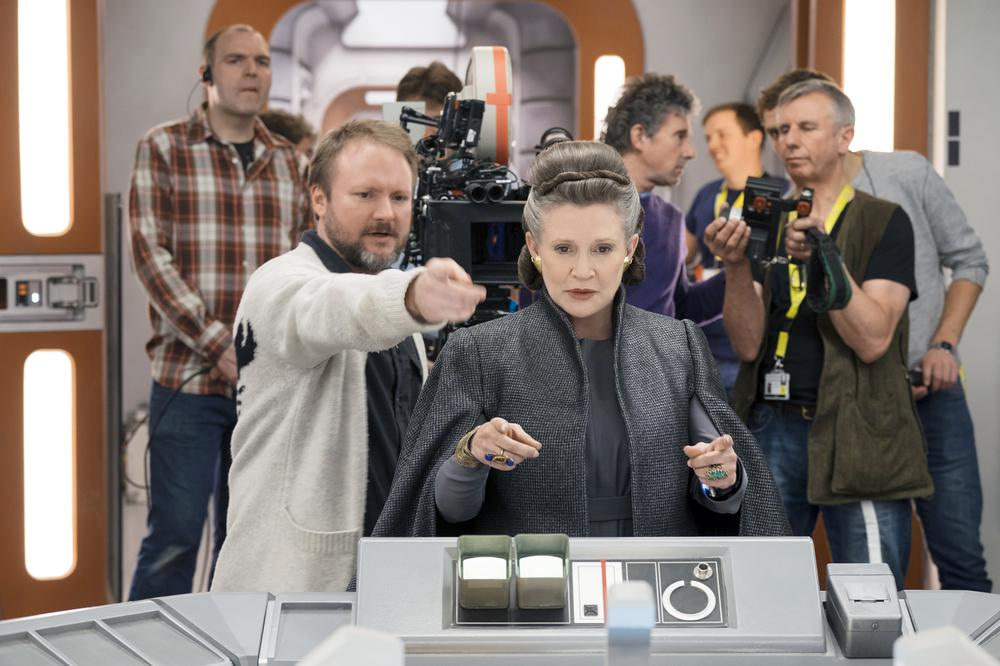 STAR WARS: THE LAST JEDI, FOREGROUND, FROM LEFT: DIRECTOR RIAN JOHNSON, CARRIE FISHER, ON SET, 2017.  PH: DAVID JAMES/© WALT DISNEY STUDIOS MOTION PICTURES/LUCASFILM LTD.