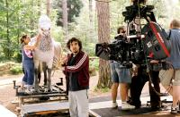 HARRY POTTER AND THE PRISONER OF AZKABAN, director Alfonso Cuaron on set, with 'Buckbeak' the Hippogriff being prepared in the background, 2004, © Warner Brothers