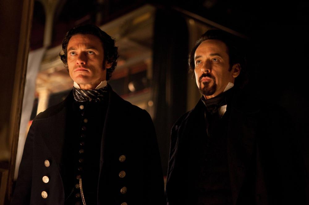 THE RAVEN, from left: Luke Evans, John Cusack, as Edgar Allan Poe, 2012. Ph: Larry Horricks/©Rogue Pictures