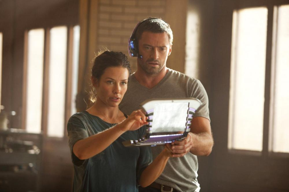 """REAL STEEL""  RS-06357R  Charlie Kenton (Hugh Jackman) and Bailey Tallet (Evangeline Lilly) study the command matrix on the controller's screen that sets the robot boxer Noisy Boy into action mode in DreamWorks Pictures' action drama ""Real Steel"".  Ph: Mel"