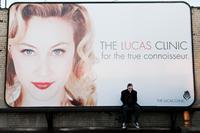 ANTIVIRAL, Sarah Gadon (on billboard), Caleb Landry Jones (sitting), 2012. ph: Caitlin Cronenberg/©IFC Midnight