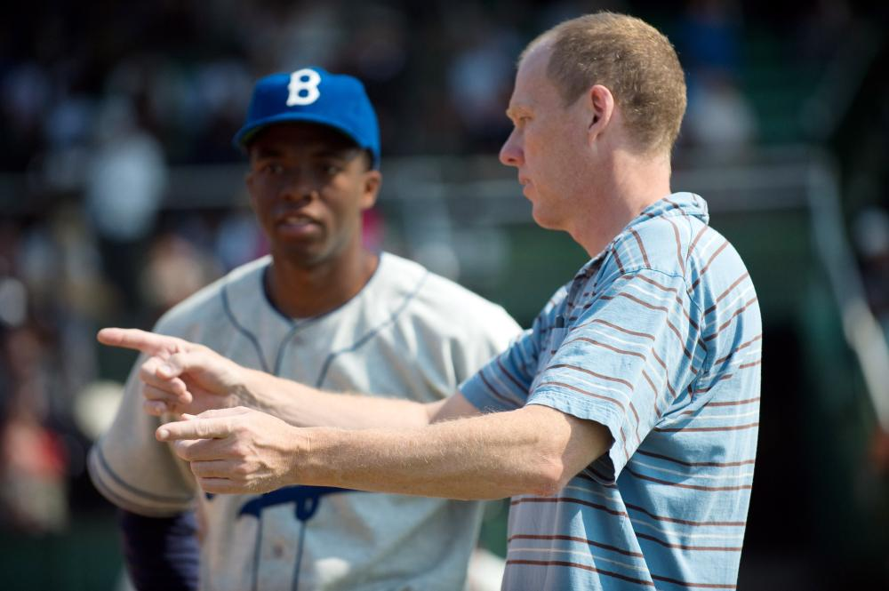42, (aka FORTY-TWO), from left: Chadwick Boseman as Jackie Robinson, director Brian Helgeland, on set, 2013. ph: D. Stevens/©Warner Bros. Pictures