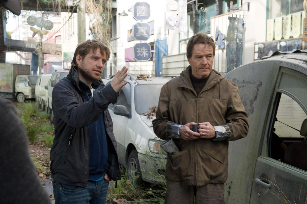 GODZILLA, from left: director Gareth Edwards, Bryan Cranston, on set, 2014. ph: Kimberley French/©Warner Bross. Pictures