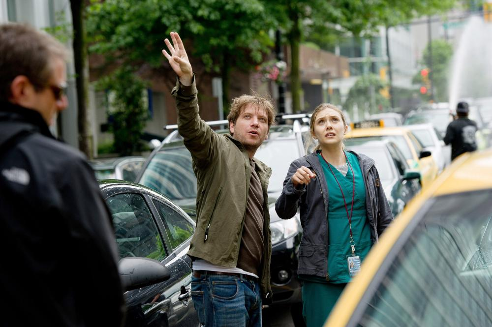 GODZILLA, from left: director Gareth Edwards, Elizabeth Olsen, on set, 2014. ph: Kimberley French/©Warner Bross. Pictures