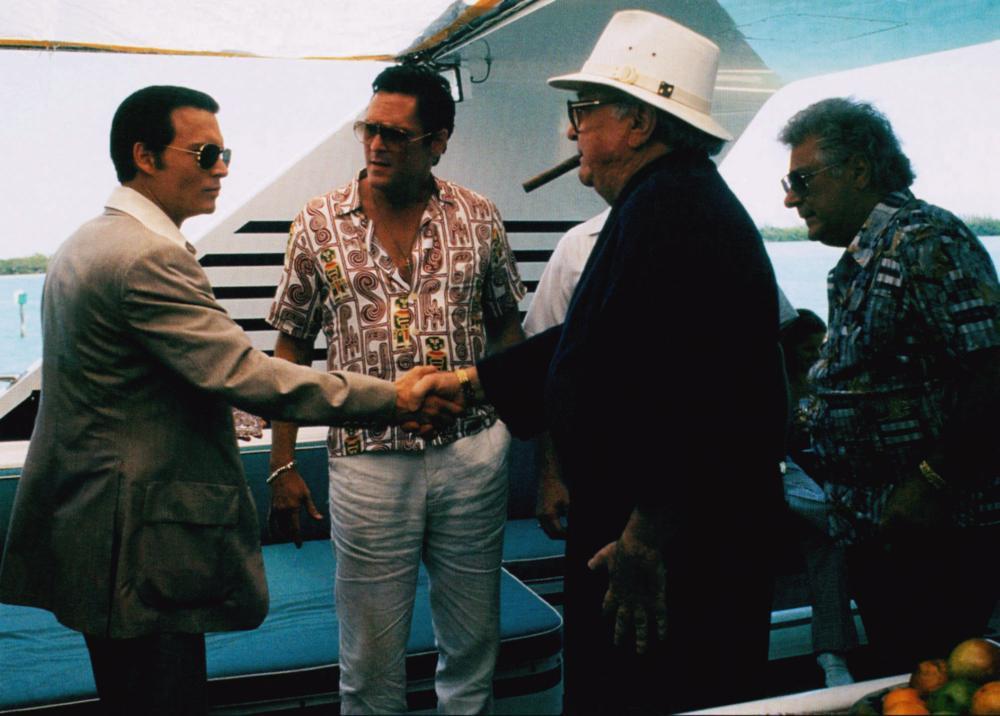 DONNIE BRASCO, shaking hands from left: Johnny Depp, Robert Miano, Michael Madsen (center), 1997, © TriStar